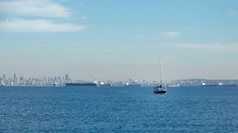 Orizzonte di Vancouver con una barca a vela e le navi di autocisterna un giorno soleggiato immagine stock libera da diritti