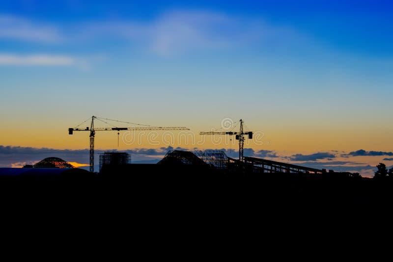 Orizzonte e siluetta del cantiere in costruzione della gru sul fondo di sera immagini stock