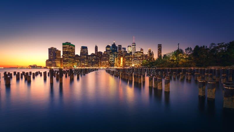 Orizzonte illuminato di Manhattan con le riflessioni New York City fotografia stock libera da diritti