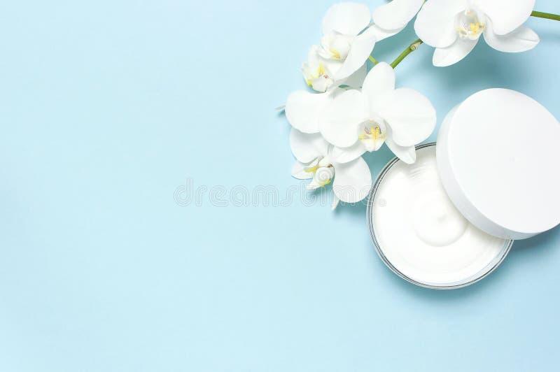 Orkid?r, stearinljus och sk?nhetsprodukter p? m?rk wood bakgrund Öppnad plast- behållare med kräm och vita Phalaenopsisorkidéblom arkivfoto