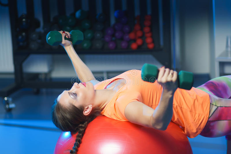 orking强有力的可爱的肌肉妇女健身的教练员w  免版税库存图片