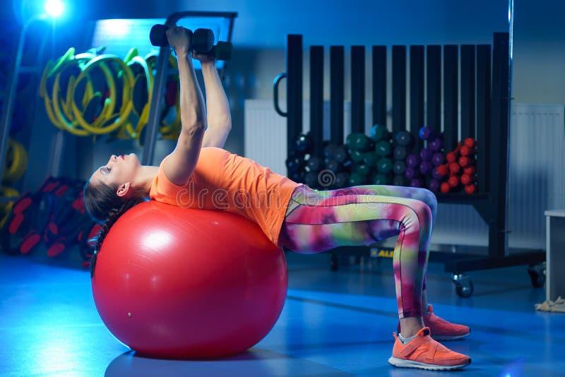 orking强有力的可爱的肌肉妇女健身的教练员w  免版税图库摄影