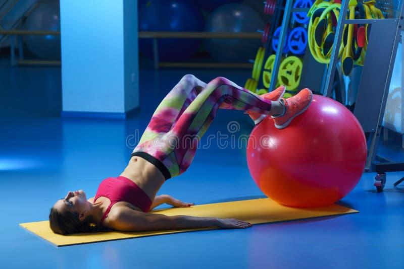 orking强有力的可爱的肌肉妇女健身的教练员w  免版税库存照片