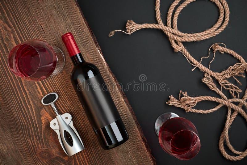 orkscrew, garrafa do vinho e dois vidros na placa de madeira no fundo preto Vista superior com espaço da cópia imagens de stock royalty free