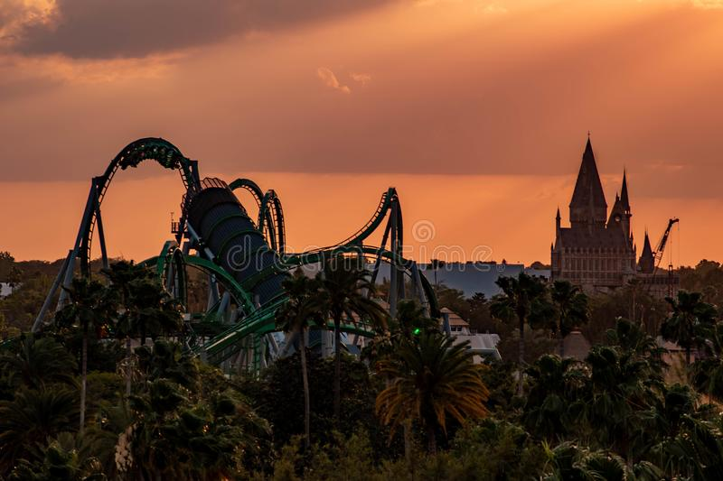 Top view of Hogwarts Castle and The Incredible Hulk rollercoaster on colorful sunset sky background at Universal Studios area. stock images
