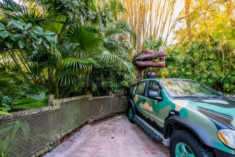 ORLANDO, FLORIDA, DE V.S. - DECEMBER, 2017: Dinosaurus tussen de struiken met zijn open mond tonend zijn tanden over een auto in  stock foto