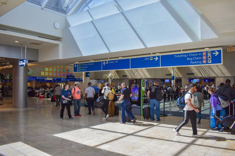 People walking to different terminals and top view of tickets and check-in blue sign at Orlando International Airport  2 stock photography