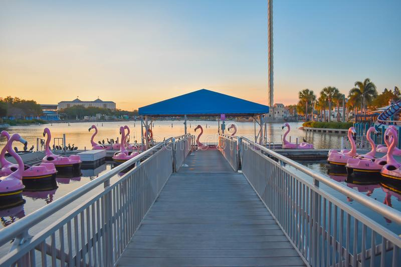 Pier and flamingo`s paddle boats on colorful sunset background at Seaworld in International Drive area 1 royalty free stock photography