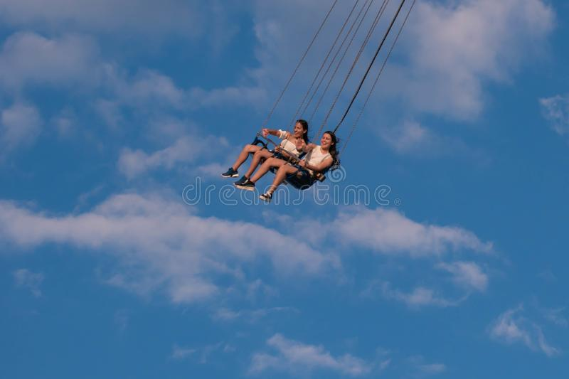 """People enjoying Orlando Star Flyer. It is the """"world's tallest swing ride standing at 450 feet.  in International Drive area. Orlando, Florida. May royalty free stock photo"""