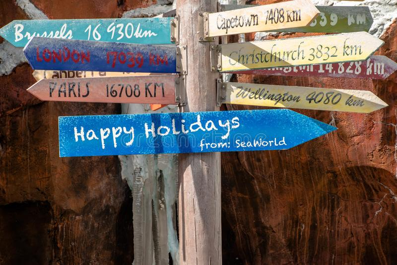 Happy Holidays and world cities distance sign at Seaworld stock image