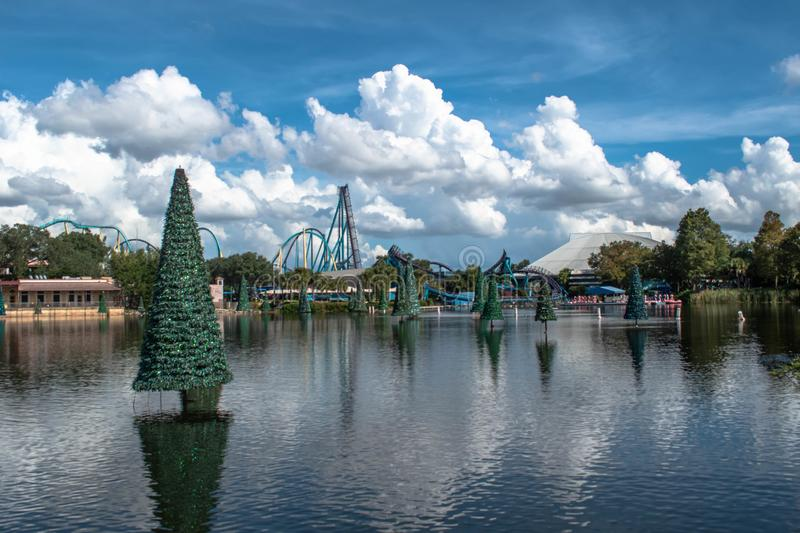 Panoramic view of Christmas trees on blue lake and rollercoaster at Seaworld 3 stock image