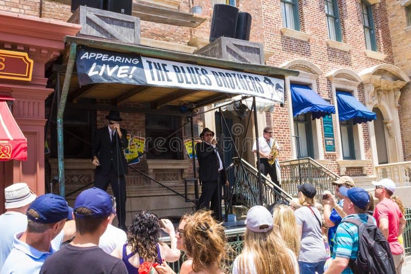 Orlando Florida, USA - Maj 10, 2018: Folket som går nära show för levande musik av deppighetbröder på, parkerar universella studi royaltyfri bild