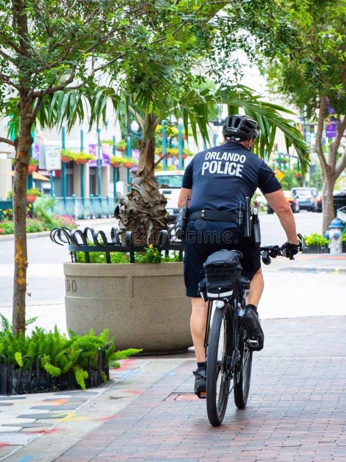 Orlando-Polizeifahrradspindel, die das Stadtzentrum patrouilliert lizenzfreie stockbilder