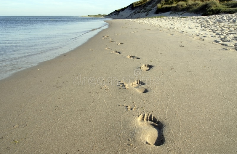 Orme alla spiaggia immagine stock