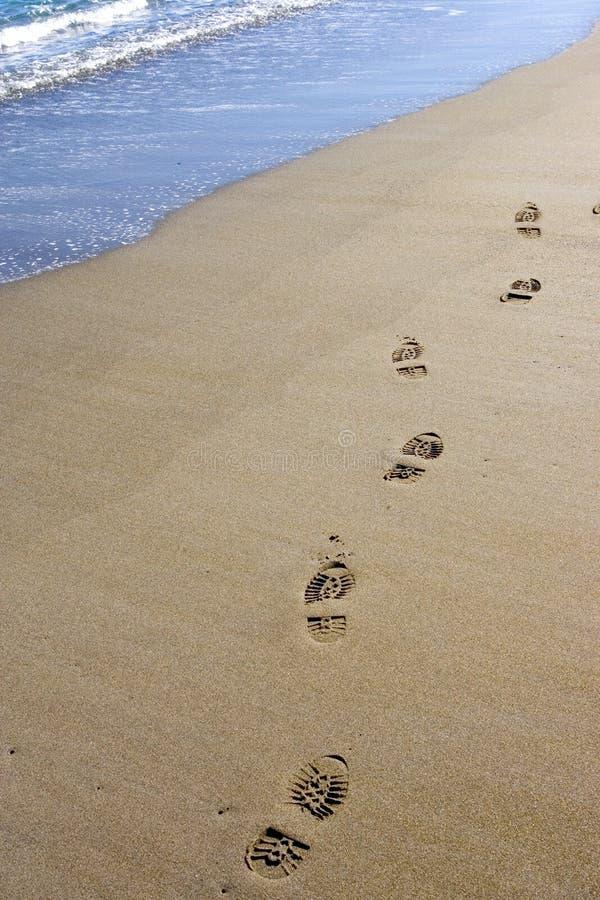 Orme sulla spiaggia sabbiosa abbandonata immagini stock