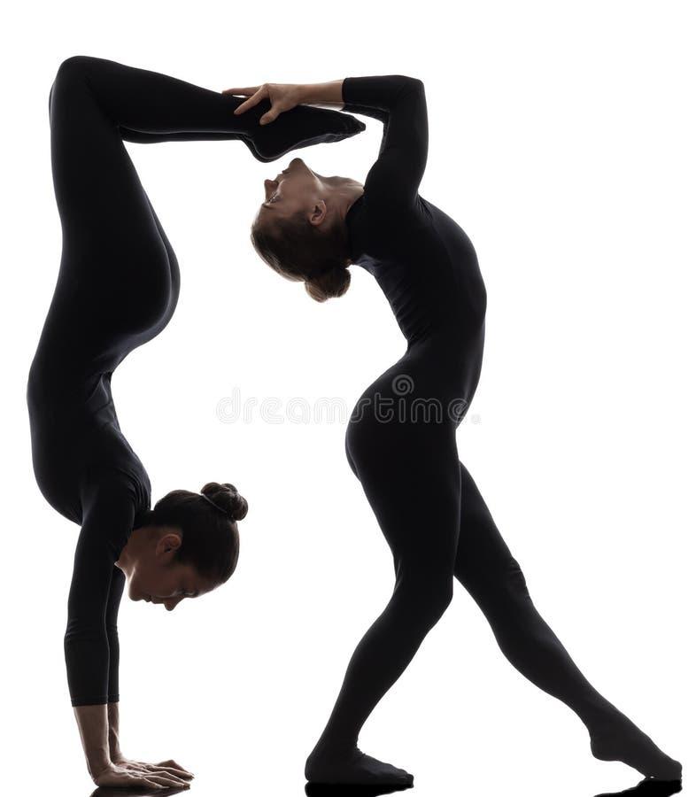 Ormmänniska för två kvinnor som övar den gymnastiska yogakonturn fotografering för bildbyråer
