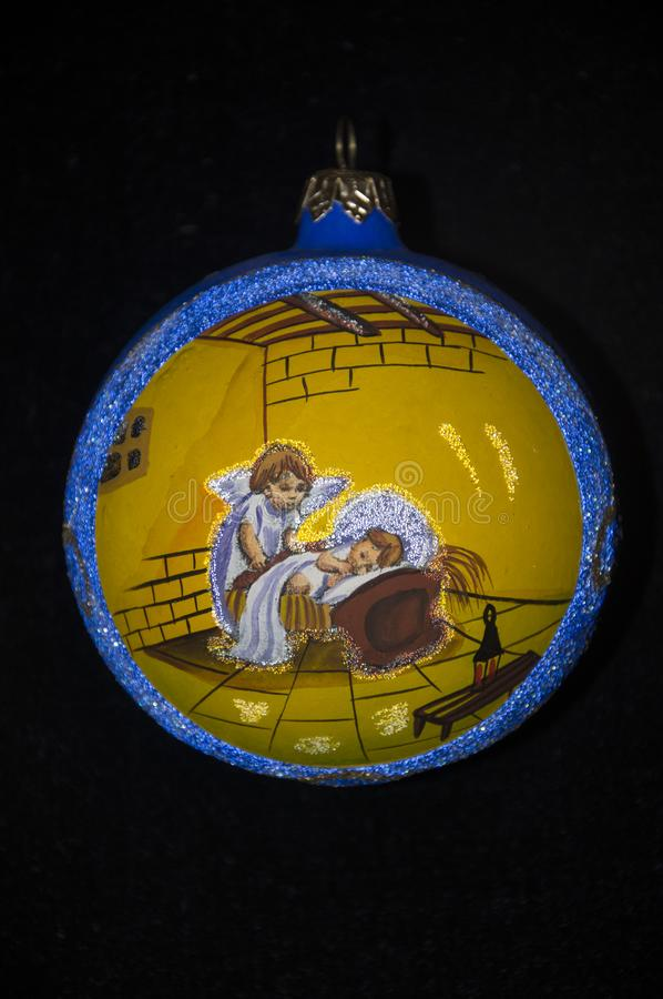 Ornament for the Christmas tree, on a black background. Angels in a yellow circle, with a blue border royalty free stock image