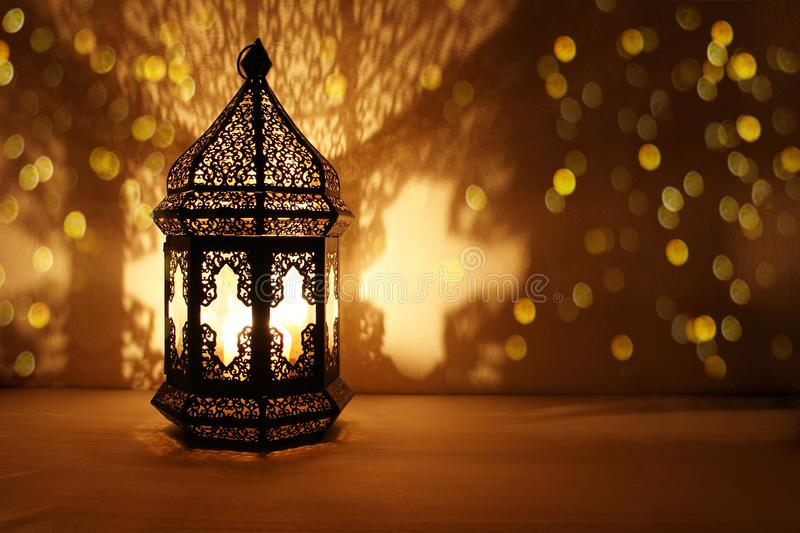 Ornamental Arabic lantern with burning candle glowing at night and glittering golden bokeh lights. Festive greeting card royalty free stock images