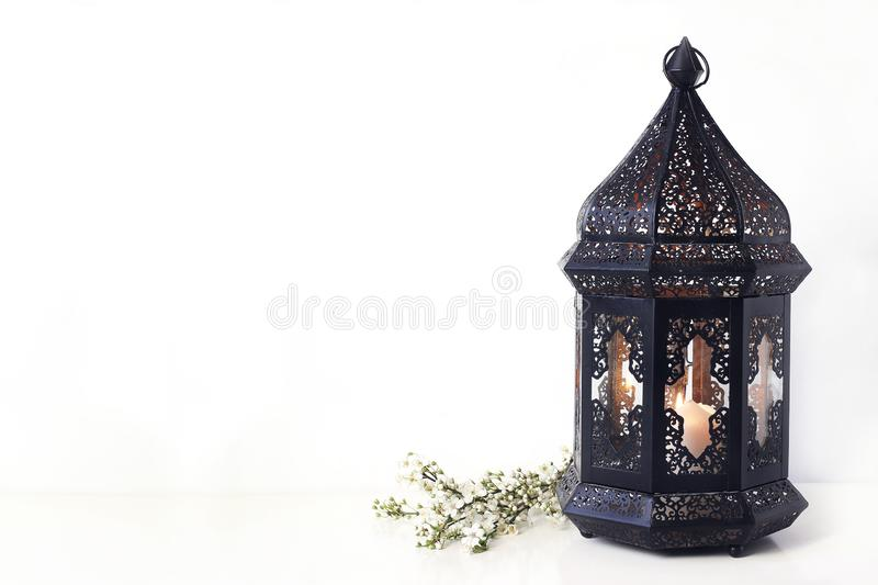 Ornamental black Moroccan, Arabic lantern with blooming prunus tree branches on white table. Greeting card for Muslim. Community holy month Ramadan Kareem royalty free stock images