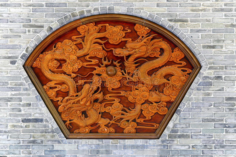 Ornamental carving of dragons on wall. Unique, ornamental carvings of two dragons on the wall stock photo
