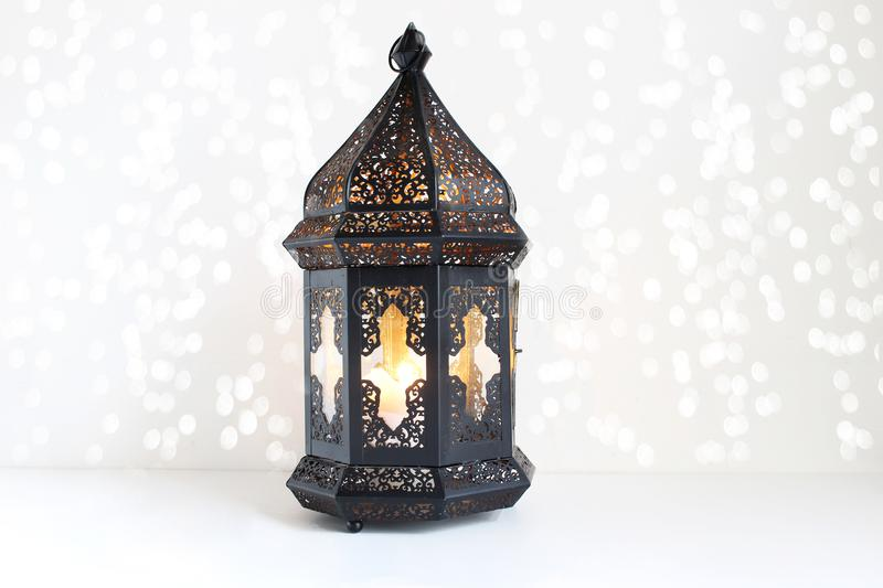 Ornamental dark Moroccan, Arabic lantern on the white table. Burning candle, glittering bokeh lights. Greeting card for. Muslim community holy month Ramadan stock photography