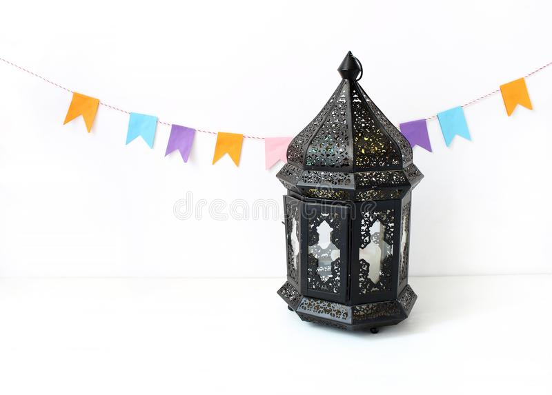 Ornamental dark Moroccan, Arabic lantern on the white table. Party decoration, string of colorful paper flags. Greeting. Ornamental dark Moroccan, Arabic lantern stock photos