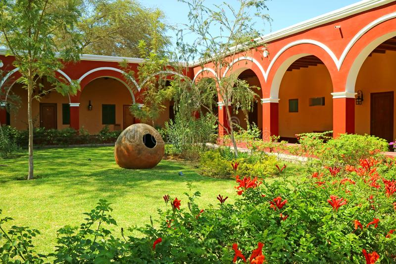 Ornamental Peruvian Garden Inside Beautiful Red and White Hallway Vintage Architecture, Huacachina Oasis Town, Ica region, Peru stock photography
