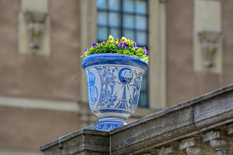 Ornamental vase with violas. On the fence of Lynx Garden Logarden at the Royal Castle in Stockholm, Sweden royalty free stock images