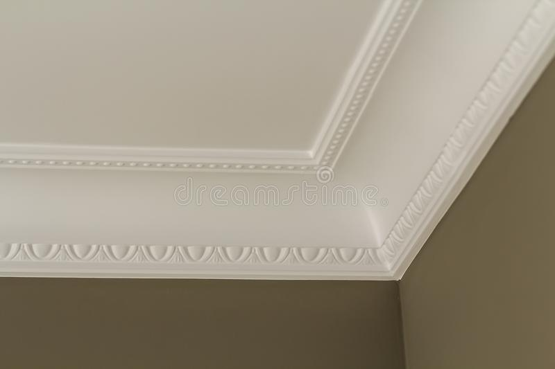 Ornamental white molding decor on ceiling of white room close-up detail. Interior renovation and construction concept. stock photography