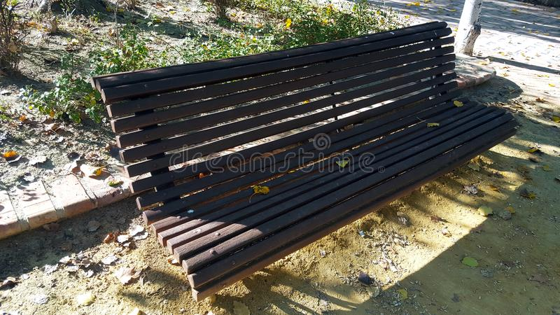 Ornamental wooden bench with horizontal slats. Herringbone brick pavement and grass behind. Autumn leaves royalty free stock images
