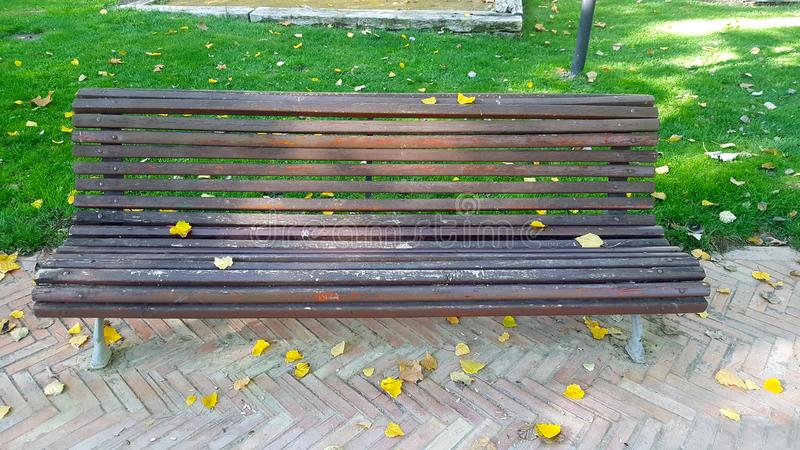 Ornamental wooden bench with horizontal slats. Herringbone brick pavement and grass behind. Autumn leaves royalty free stock photo