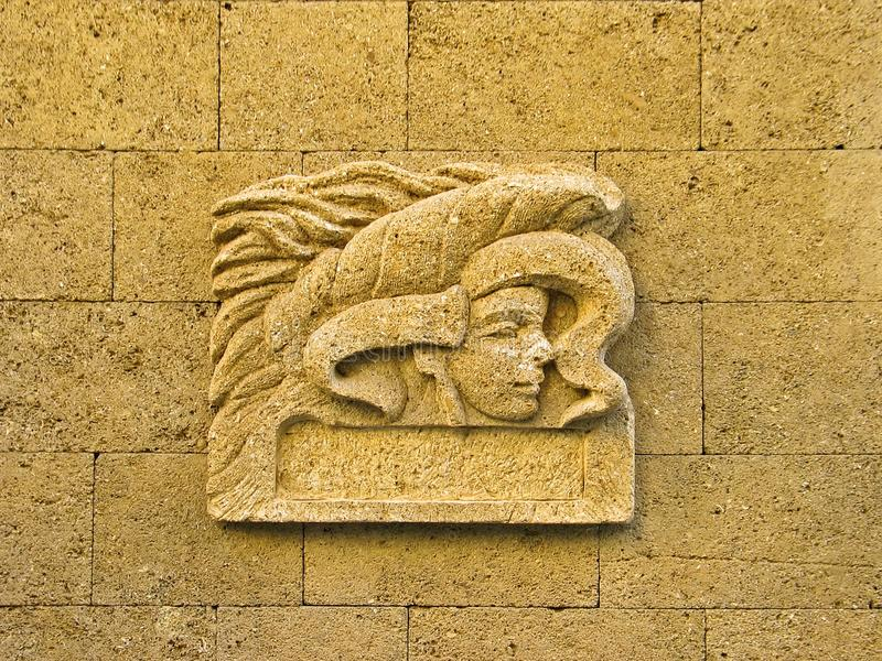 Ornamentation. A carved face symbolizes a fruitfulness goddess embossed on a sandstone wall in Aix-en-Provence in France stock photo