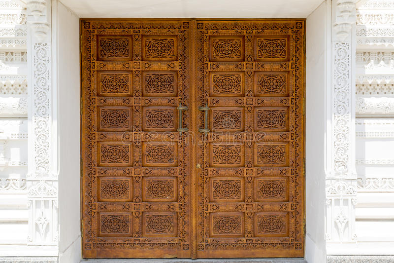 Ornamented door. Ornated wooden front door in a hindu temple stock images
