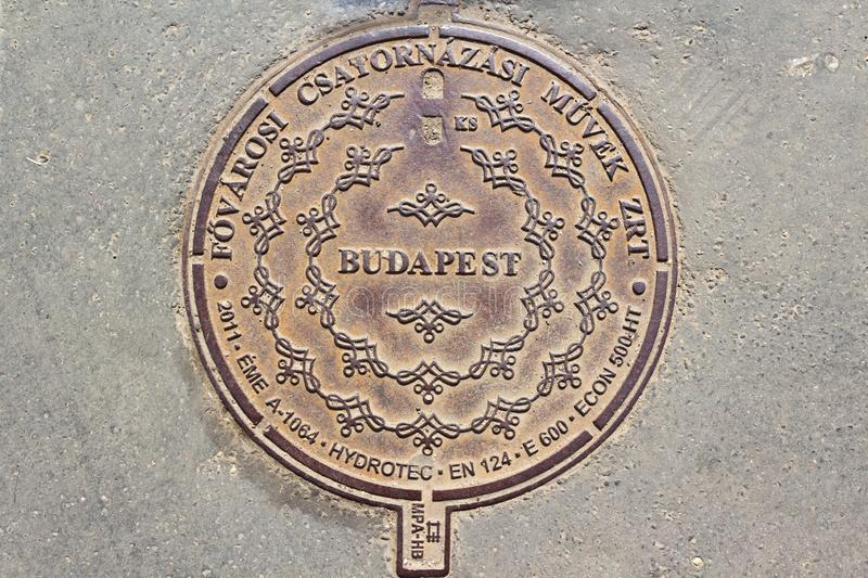 Ornamented manhole cover in Budapest, Hungary. Ornamented cast-iron drain cover in Budapest, Hungary. Text is: Budapest Sewage Pte Ltd stock images