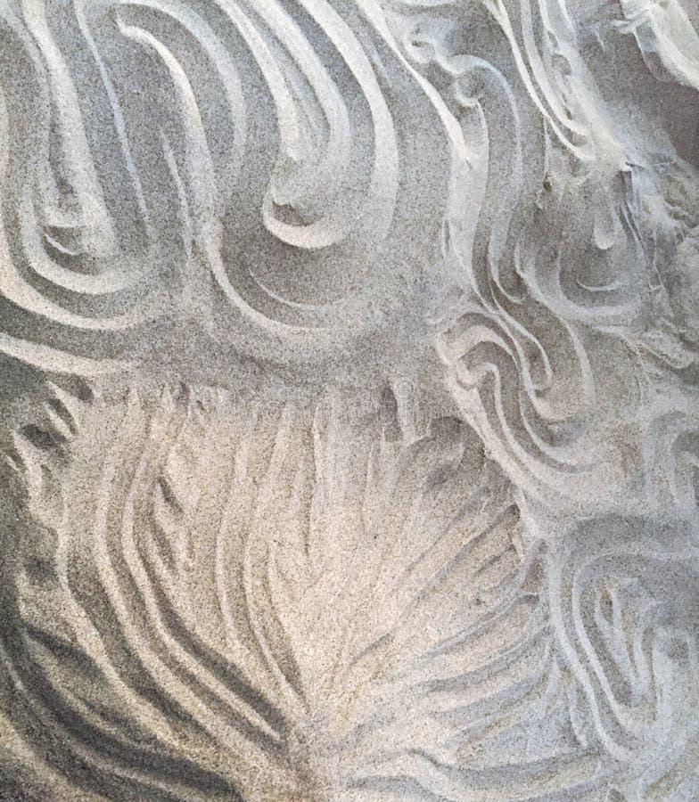 Ornamenten die op wit zand worden getrokken De witte tekening van strandmandala royalty-vrije stock fotografie