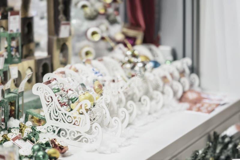 Ornamenten, Kerstmisballen en witte houten sleeën Verkoop van Kerstmisdecoratie Abstracte licht vage vakantie royalty-vrije stock afbeeldingen