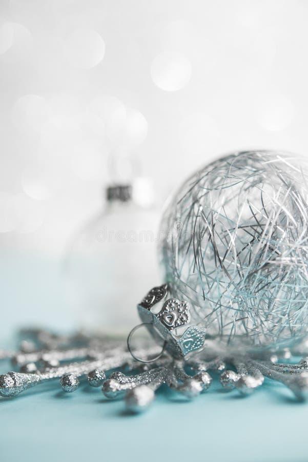 Ornamenti bianchi e d'argento di natale sul fondo del bokeh di scintillio Carta di Buon Natale fotografia stock libera da diritti