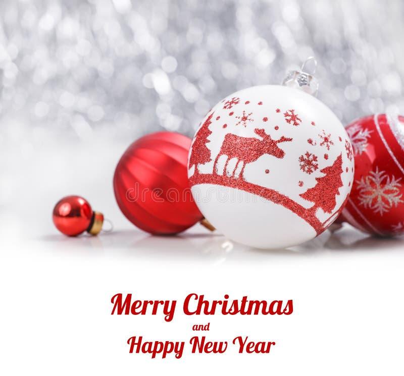 Ornamenti bianchi e rossi di Natale sul fondo del bokeh di scintillio con spazio per testo Carta del buon anno e di natale fotografie stock