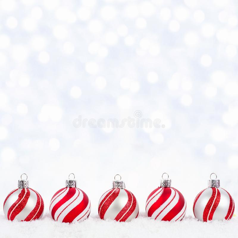 Ornamenti di natale bianco e di rosso in neve con il fondo di twinkling immagine stock
