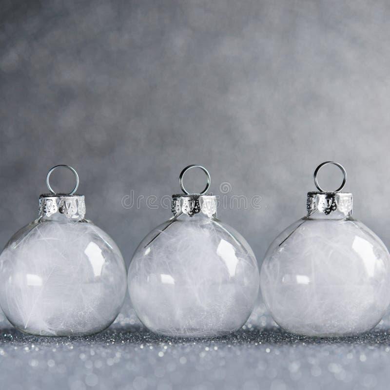 Ornamenti di natale bianco sul fondo d'argento di scintillio con spazio per testo immagini stock