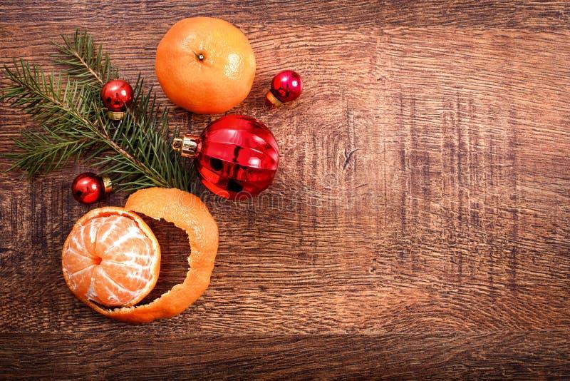 Ornamenti di Natale, decorazione dell'alimento e ramo di albero rossi dell'abete su un fondo di legno rustico fotografia stock libera da diritti