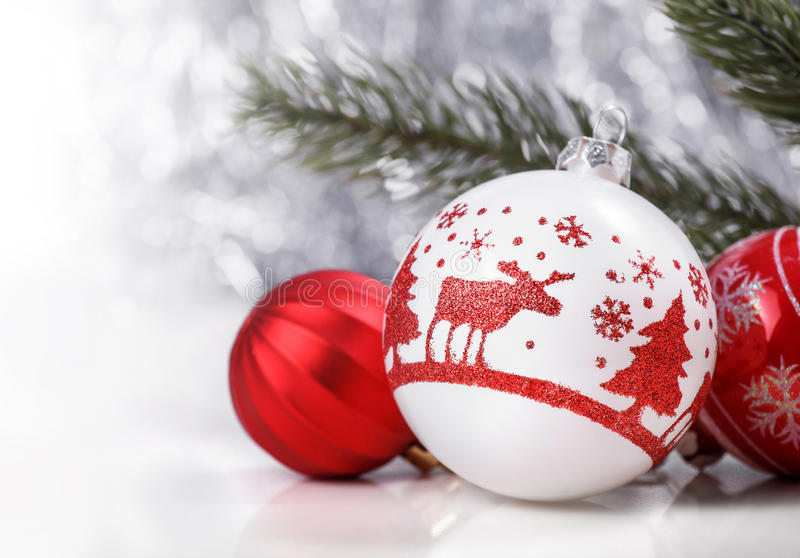 Ornamenti di Natale e ramo di albero bianchi e rossi dell'abete sul fondo del bokeh di scintillio con spazio per testo Natale e b fotografia stock libera da diritti