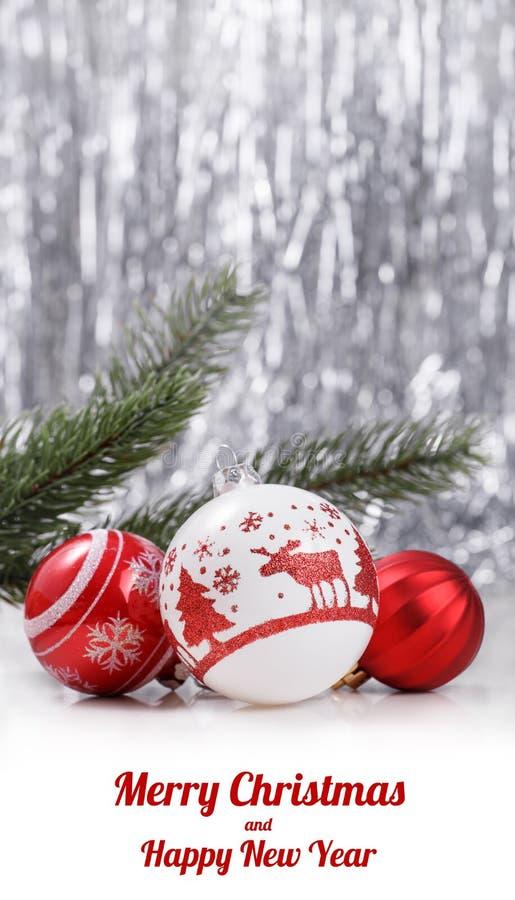 Ornamenti di Natale e ramo di albero bianchi e rossi dell'abete sul fondo del bokeh di scintillio con spazio per testo Natale e b immagini stock