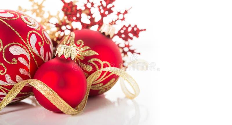 Ornamenti dorati e rossi di natale su fondo bianco Carta di Buon Natale immagini stock libere da diritti