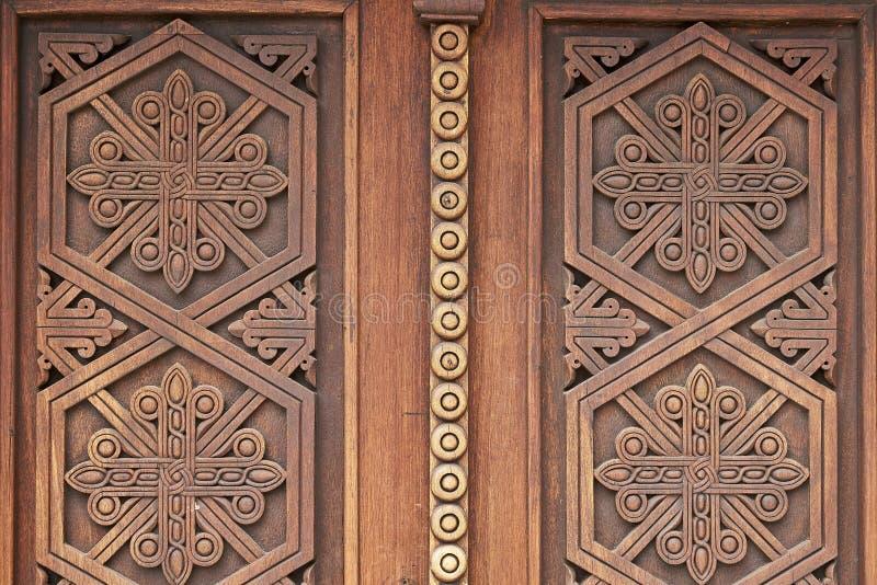 Ornamenti sulle porte di legno della chiesa in monastero medievale armeno fotografia stock libera da diritti