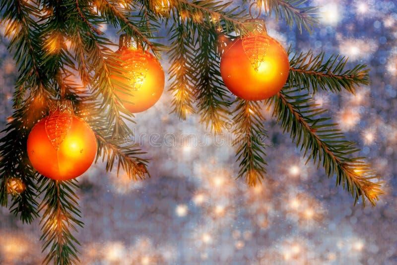 Ornamento alaranjados do Natal em ramos do abeto vermelho em um fundo brilhante da azul-prata O fundo de ano novo ou de Natal imagens de stock