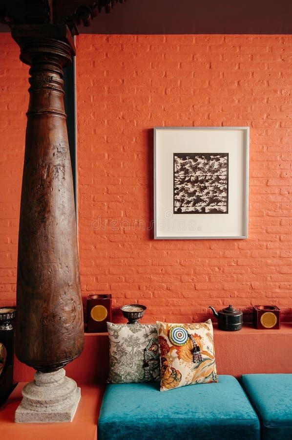 Ornamento antico della decorazione domestica d'annata asiatica, palo di legno, muro di mattoni colourful, cuscini e cusion immagine stock libera da diritti