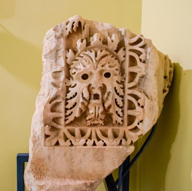 Ornamento antiguo sobre puertas de la puerta, caras con las bocas abiertas y pelo rizado foto de archivo libre de regalías