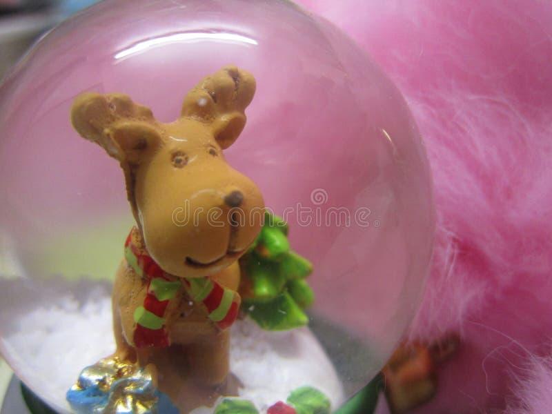 Ornamento bonito del globo de la nieve del reno de la Navidad contra fondo rosado de la piel imagen de archivo