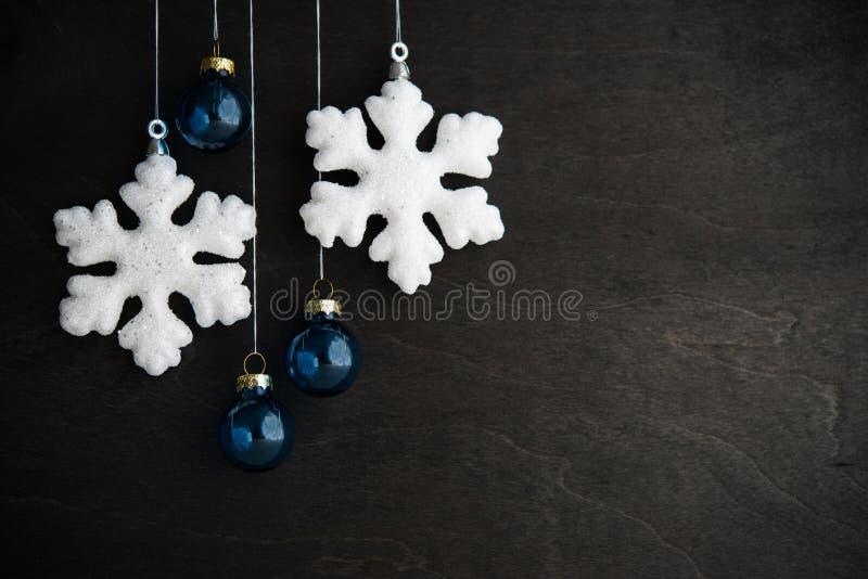 Ornamento brancos e azuis do xmas no fundo de madeira preto Cartão do Feliz Natal imagens de stock